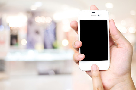 departmentstore: Hand holding smart phone over blur store background, e-commerce, business and technology concept Stock Photo