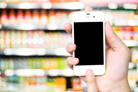 Hand holding smart phone over blur supermarket background, e-commerce, business and technology concept