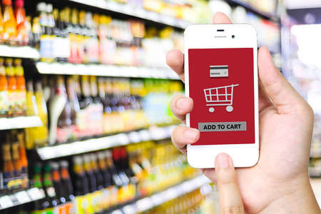 add: Hand holding smart phone with add to cart words on screen over blur supermarket background, e-commerce, business and technology concept