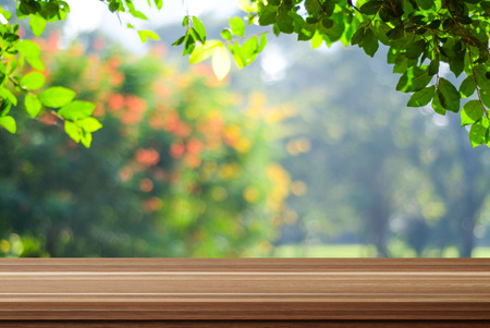Empty wooden deck table over blurred tree with bokeh background, for product display montage