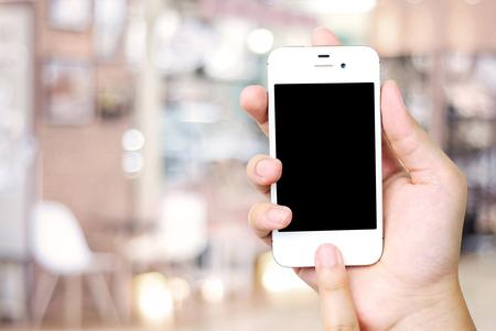 Hand holding smart phone over blur restaurant background, restaurant reservation, food online, food delivery concept Foto de archivo