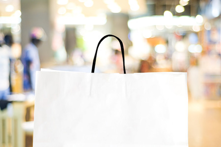 retail business: White shopping bag over blurred store background, business, template, retail, sale