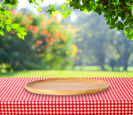montage: Empty round wooden tray on table over blur trees with bokeh background, for product display montage