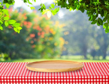 Lege ronde houten dienblad op tafel over onscherpte bomen met bokeh achtergrond, voor product-display montage Stockfoto
