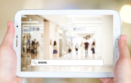screen search: Hand holding tablet with www. on search bar over blur store background on screen, on line shopping ,business, E-commerce, technology and digital marketing background