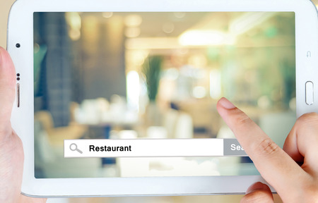 restaurant: Hand holding tablet with restaurant word on search bar over blur restaurant background on screen, restaurant reservation, food online, food delivery concept
