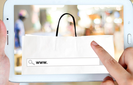 e shop: Hand holding tablet with www. on search bar over shopping bag and blur store background on screen, on line shopping ,business, E-commerce, technology and digital marketing background Stock Photo