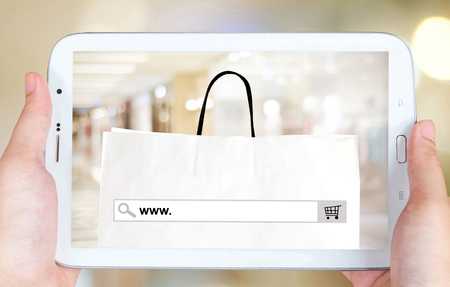 internet store: Hand holding tablet with www. on search bar over blur store background on screen, on line shopping ,business, E-commerce, technology and digital marketing background