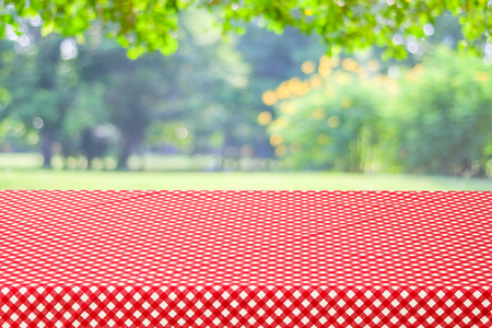 picknick: Empty table and red tablecloth with blur green leaves bokeh background, for product display montage