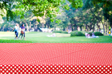 picknick: Empty table and red tablecloth over blur park with people background, for product display montage