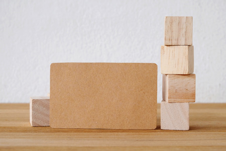 wood craft: Blank recycle paper business card and wooden cubes on table and cement wall background, template, mock up