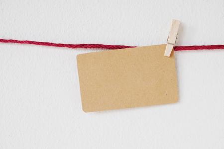 reciclar: En blanco tarjeta de papel reciclado que cuelga en cuerda para tender rojo sobre blanco la pared de cemento, fondo, plantilla