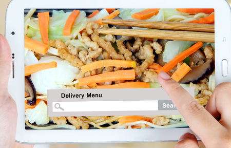 Hand holding tablet with food delivery menu on search bar, food online, food delivery concept