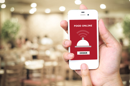 comida: Mano que sostiene el tel�fono inteligente con el dispositivo de alimentaci�n en l�nea en la pantalla sobre el restaurante desenfoque de fondo, la comida en l�nea, el concepto de la entrega de alimentos