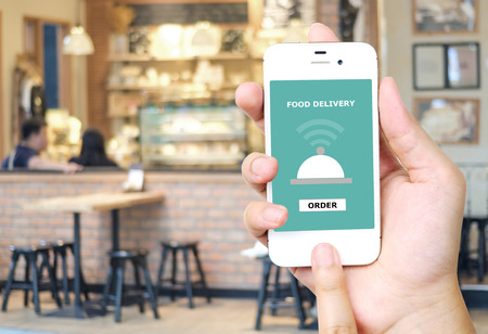 ordering: Hand holding smart phone with food delivery device on screen over blur restaurant background, food online, food delivery concept