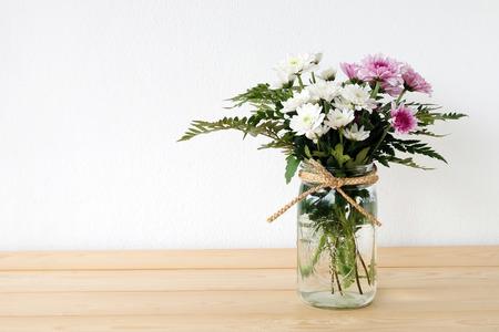 frasco: Blanco y ramo de la margarita de color rosa en el tarro de albañil en el fondo de la tabla, flores frescas Foto de archivo