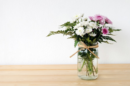 jar: White and pink daisy bouquet in mason jar on table background, fresh flower