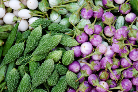 green and purple vegetables: Bitter gourds, Momordica charantia, and white, green, purple egg plants, fresh vegetables, top view Stock Photo