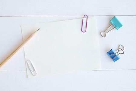 lapiz y papel: Papel en blanco nota, lápiz y clips de colores en el fondo de madera blanco, plantilla para el texto