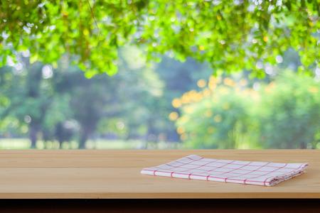 manteles: Blanco y rojo de tela de tart�n en la mesa de madera sobre fondo borroso jard�n, exhibici�n de alimentos montaje Foto de archivo