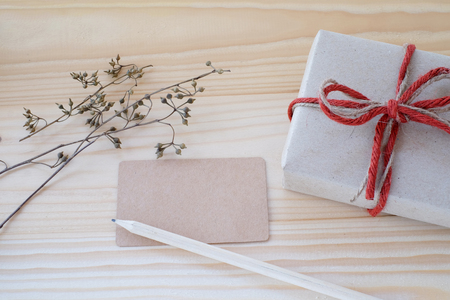 text space: Vintage gift box, blank card and pencil on wood background, copy space