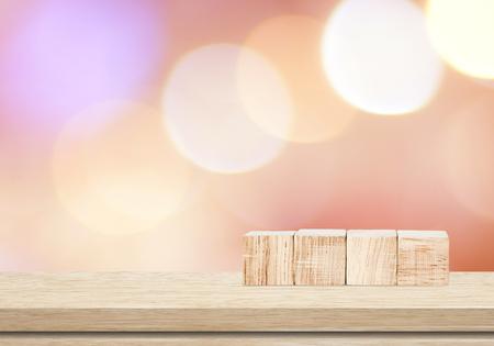 Vier houten kubussen op tafel over blur abstract bokeh lichte achtergrond Stockfoto