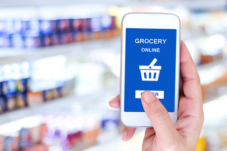 grocery shelves: Hand holding smart phone with grocery shopping online on screen over blur supermarket background, retail business and technology concept Stock Photo