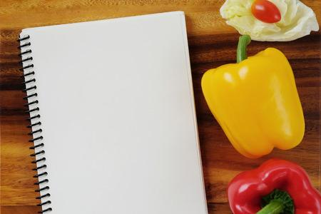 hoja en blanco: Los pimientos verdes, repollo, tomates y el cuaderno en blanco sobre fondo de madera