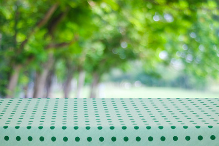 picknick: Empty table with green tablecloth over blur garden and bokeh background, for food and product display montage Stock Photo