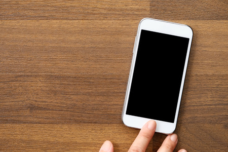 hand lay: Smart phone and hand on wood background with copy space, flat lay Stock Photo