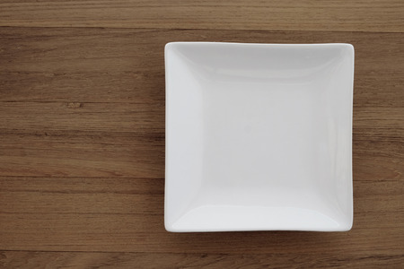Empty square white plate in wood background, food display montage, flat lay, top view