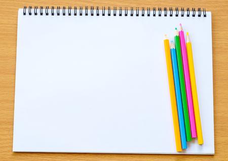 hoja en blanco: bloc de notas en blanco y lápiz de color sobre la mesa de madera Foto de archivo