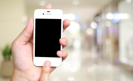centro comercial: teléfono inteligente en la mano en la tienda de la falta de definición con el fondo bokeh, los negocios, el concepto de tecnología