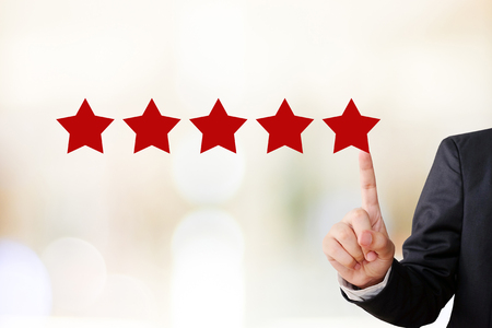 five star: Businessman hand pointing five star, customer satisfaction concept, business background Stock Photo