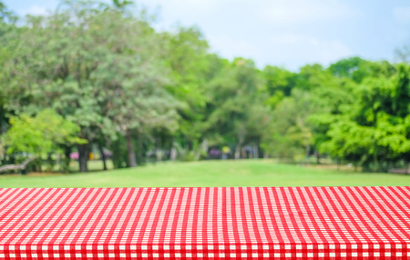 picknick: Empty table with red tablecloth over blur garden and bokeh background, for food and product display montage Stock Photo