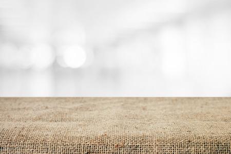 Leere Tisch- und Sacktischdecke über Unschärfe abstraktem bokeh hellem Hintergrund, Produktanzeigenmontage, Weinleseart