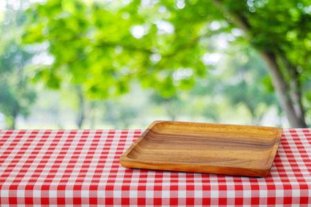 food tray: Empty wooden tray on table over blur trees with bokeh background, for food and product display montage