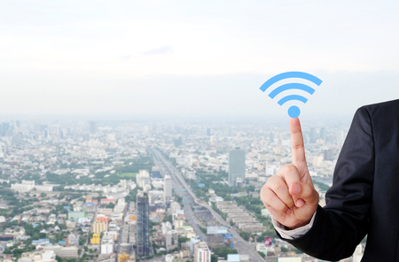 to scrape: Businessman hand pointing wifi icon over blur city scrape background, internet of things concept Stock Photo