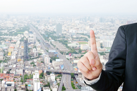 to scrape: Businessman hand pointing over blur city scrape background, business concept Stock Photo
