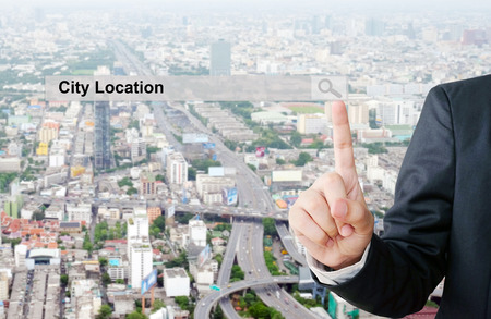 to scrape: Businessman hand pointing city location search bar over blur city scrape background, business and technology concept