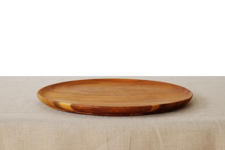 bandeja vacía redonda de madera sobre mantel de lino aislado en el fondo blanco, montaje alimentos, plantilla