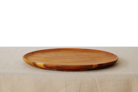 Empty round wooden tray on linen tablecloth isolated on white background, food montage, template Foto de archivo