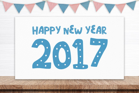 celebrate year: Happy new year 2017 on white board and party flags hanging on white wood background