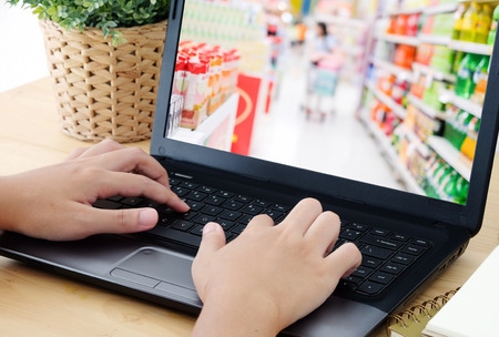 Hand typing labtop with blur supermarket on screen , Grocery online concept, business and technology
