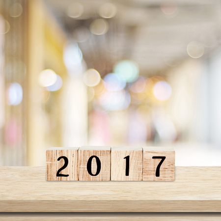 Wooden cubes with 2017 on table over blur bokeh background with copy space for text, new year template