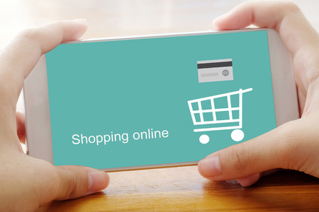 ebuy: Hand holding smart phone with shopping online screen background, business, E-commerce, technology and digital marketing Stock Photo