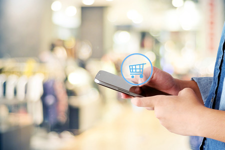 ebuy: Woman hand using smart phone and shopping icon over blur store with bokeh background, business and technology concept, digital marketing