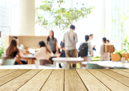 Empty wood perspective,table top, over blur group of people team meeting at co-working space background, teamwork, business and education concept , template, for product display montage Stock Photo