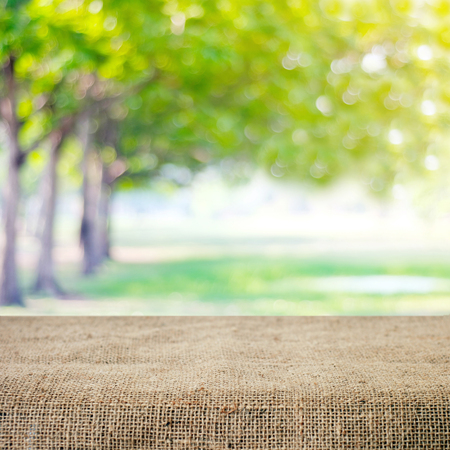 picknick: Empty table and sack tablecloth over blur tree with bokeh background, for product display montage