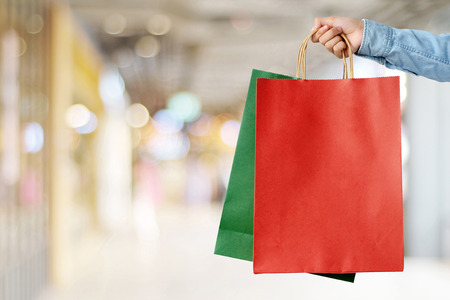 shopper: Hand holding red shopping bag on blur store background, banner with copy space for text, template, business concept